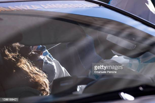 "An Italian military nurse swabs a member of the public during the ""Drive-Through-Defense"" of Operation ""IGEA"" commissioned by the Minister of Defense..."
