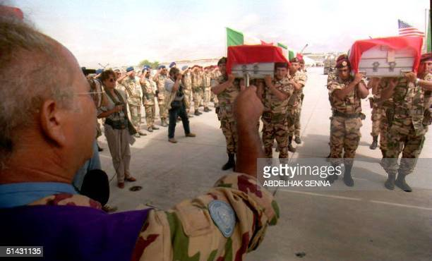 An Italian military priest blesses the coffins of two slain Italian UN soldiers at Mogadishu airport 16 September 1993 as over a hundred UN soldiers...
