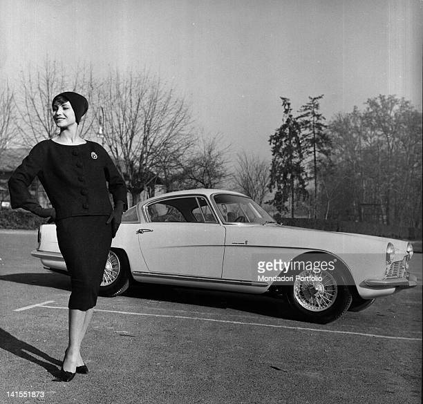 An Italian model wearing a collarless suit in front of a car Italy 1958