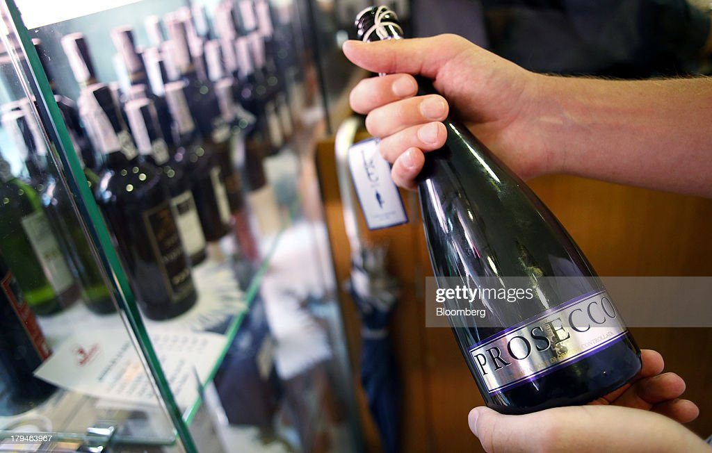 An Italian oenologist checks a bottle of Prosecco wine for authenticity at a food store in Treviso, Italy, on Tuesday, Sept. 3, 2013. Italy's Agriculture Ministry has begun to investigate suspected sales of imitation Prosecco sparkling wine in its native Veneto region. Photographer: Alessia Pierdomenico/Bloomberg via Getty Images