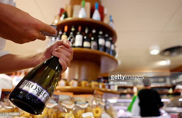 An Italian oenologist checks a bottle of Prosecco wine for authenticity at a food store in Treviso Italy on Tuesday Sept 3 2013 Italy's Agriculture...
