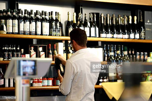An Italian oenologist checks bottles of Prosecco wine for authenticity at a food and drinks store in Treviso Italy on Tuesday Sept 3 2013 Italy's...