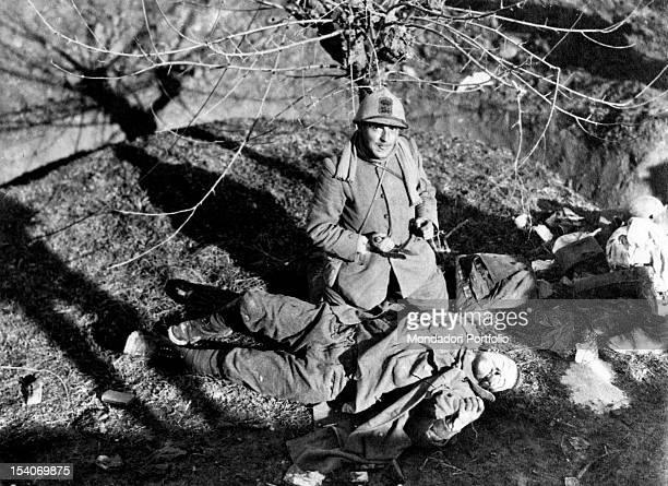 An Italian officer kneeling near an Austrian soldier fallen in a battle on the Piave front. Veneto, 1918