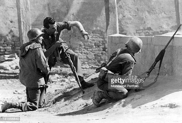 An Italian partisan showing the position of the German soldiers to two U.S. Soldiers of the Fifth Allied Army. Modena, April 1945