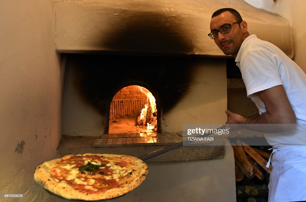 An Italian 'Pizzaiolo' (pizza maker) prepares a Pizza Margherita in the first stone oven where was cooked a Pizza Margherita at the Capodimonte museum, on December 6, 2017 in Naples. Naples' art of pizza twirling is a candidate to join UNESCO's list of 'intangible heritage' and the city is waiting for the decision of the UN cultural body's World Heritage Committee which is reunited in South Korean island of Jeju this week. /