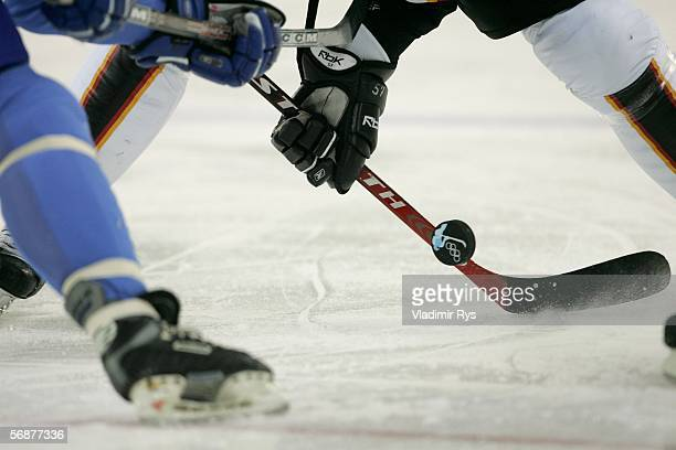 An Italian player fights for the puck with a German player during the men's ice hockey Preliminary Round Group A match between Italy and Germany...
