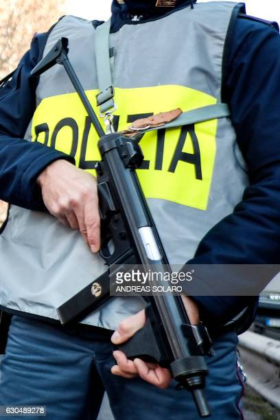 An Italian police officer holds a weapon as he stands guard at a security checkpoint in a central street of Rome on December 24 2016 / AFP / Andreas...