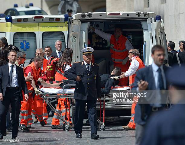 An Italian policeman is carried away by paramedics after two policemen were wounded on April 28 2013 during a shooting outside the palazzo Chigi the...