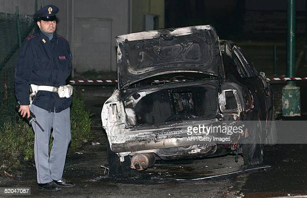 An Italian policeman stands guard in front of the burned car of Giulio Ruggiero decapitated and burned in his car in Naples, 22 January 2005. The...
