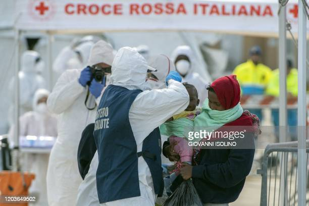 An Italian Red Cross' agent wearing protective suit and mask takes a picture and a Italian Health ministry's agent take a child's temperature as...