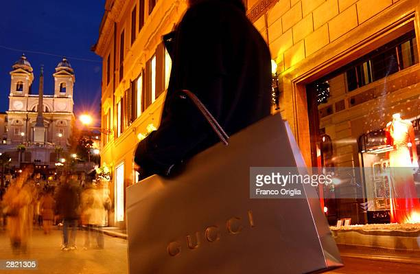 An Italian shopper carries a Gucci bag as shoppers browse for Christmas gifts at Via Condotti which is the home to some of the world's most famous...