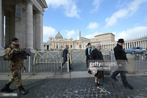 An Italian soldier and passersby walk as a police vehicle drives past a deserted St Peter's square at the Vatican on March 6 2020 The Vatican on...