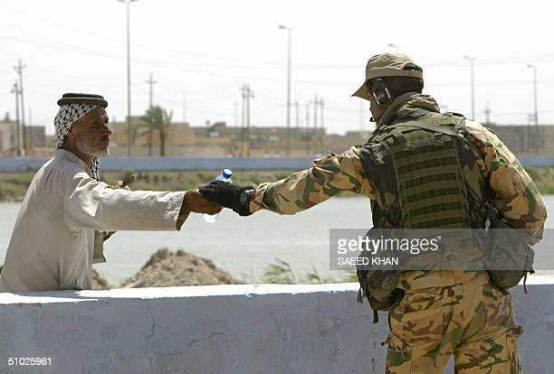 An Italian soldier gives a bottle of cold mineral water to an Iraqi Shiite Muslim man as he patrols the town of Nassiriyah, 375 kms southeast Baghdad...