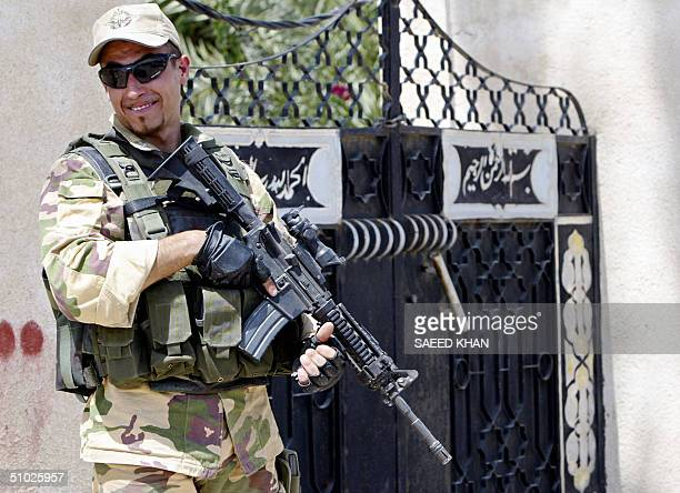An Italian soldier smiles to one of his colleagues as they patrol the town of Nassiriyah, 375 kms southeast Baghdad 05 July 2004. Italy has nearly...