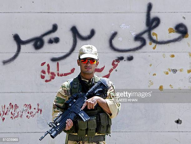"""An Italian soldier stands guard in front of a graffiti reading in Arabic, """"Paul Bremer is a donkey"""", as he patrol the town of Nassiriyah, 375 kms..."""