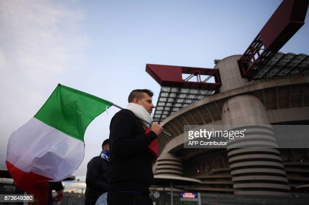 An Italian supporter holds a flag as he arrives at the San Siro Stadium before the FIFA World Cup 2018 qualification football match between Italy and...