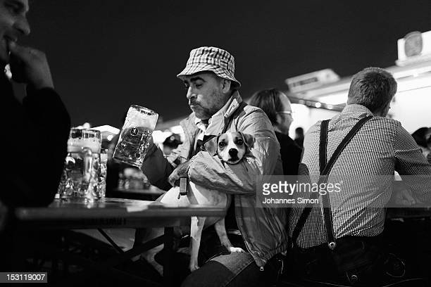 An Italian tourist enjoys a beer with his dog in the night time of day 9 of the Oktoberfest beer festival on September 30 2012 in Munich Germany This...