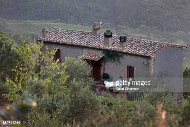 An Italian woman sits outside her farmhouse at dusk on July 23 2015 near the hilltop town of Montalcino in the region of Tuscany Italy Tuscany is...