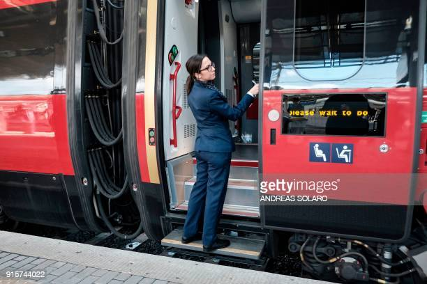 An Italo staff member looks on as people wait to board an Italo NTV train at the Tiburtina railway station in central Rome on February 8 2018 The...