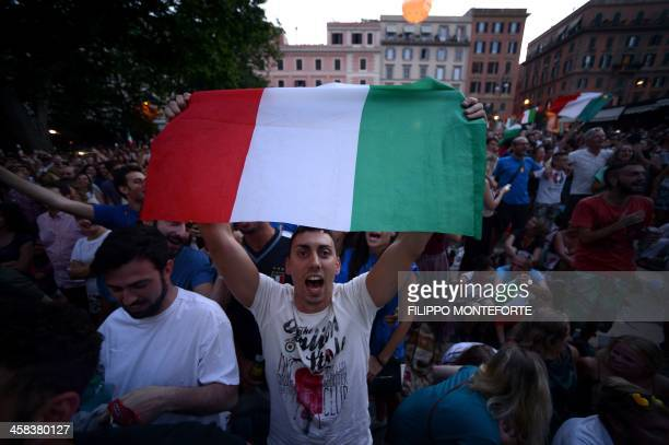 An Italy fan waves an Italian flag in Rome's Trastevere neighborhood on July 2 2016 as he watches the Euro 2016 quarterfinal football match between...