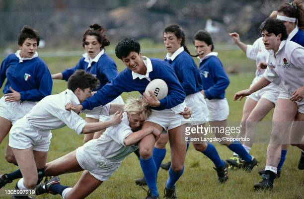 An Italy player is tackled for possession of the ball during play in the pool 4 match between England and Italy on the second day of competition in...