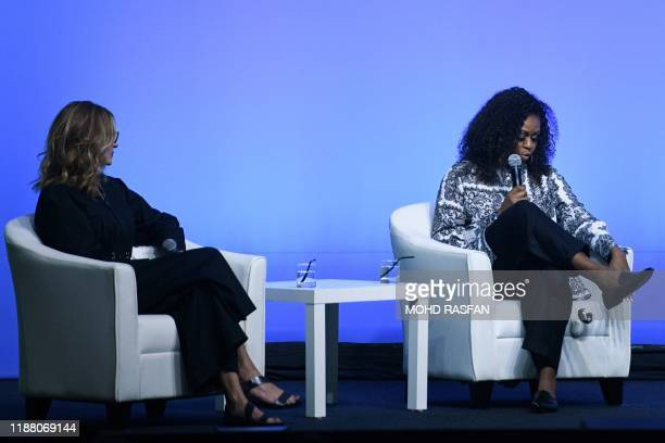 An item falls down from former US first lady Michelle Obama as US actress Julia Roberts looks on as they attend an event for the Obama Foundation in...