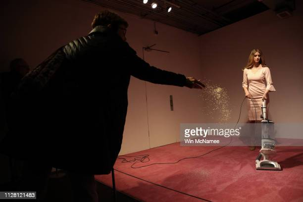 An Ivanka Trump lookalike model vacuums bread crumbs thrown by visitors as part of an art installation titled Ivanka Vacuuming at the Flashpoint...