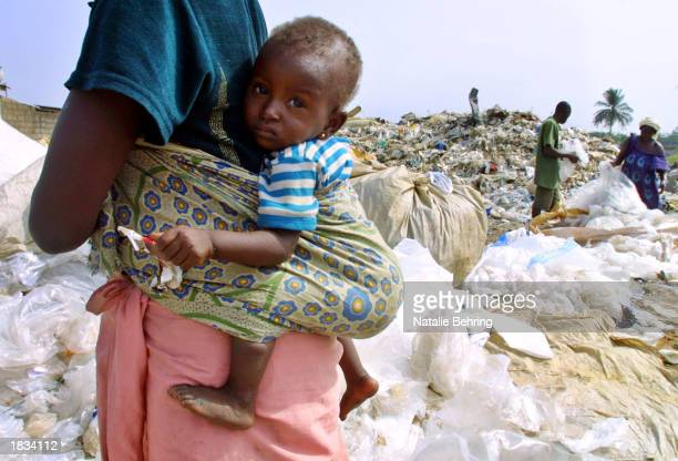 An Ivorian mother carries her child strapped her back as she sifts through garbage to scavenge for plastic to sell in a demolished shanty town March...