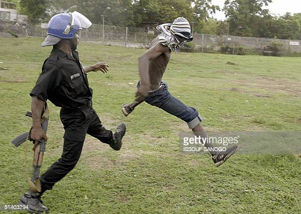 An Ivorian policeman tries to arrest a demonstrator who was throwing stones to French gendarmes 05 October 2004 during a protest at the French...