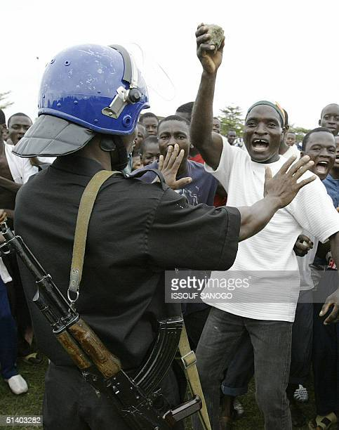 An Ivorian policeman tries to calm down demonstrators throwing stones to French gendarmes 05 October 2004 during a protest at the French military...