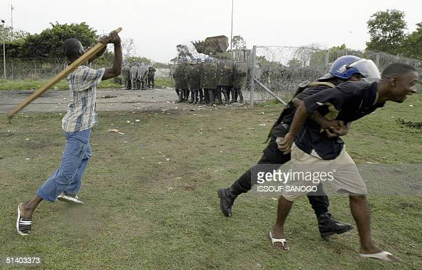 An Ivorian policeman tries to prevent demonstrators from throwing stones to French gendarmes 05 October 2004 during a protest at the French military...