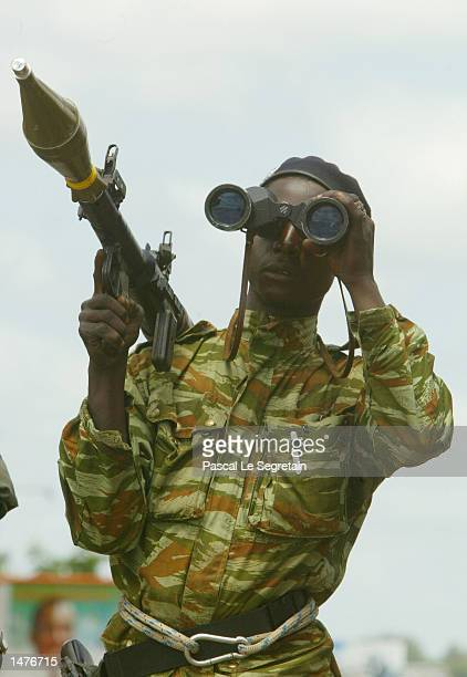 An Ivorian rebel soldier patrols on top a fourwheel drive vehicle looking through binoculars at the south road to Yamoussoukro at the southern check...