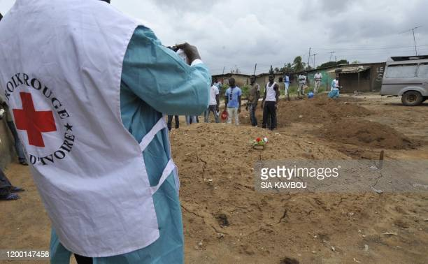 An Ivorian Red Cross worker photographs an area claimed to be a mass grave on May 4, 2011 during a mission to collect corpses in Yopougon, a district...