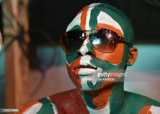 An Ivorian supporter watches on a giant screen the 2015 Africa Cup of Nations football final in Equatorial Guinea between Ivory Coast and Ghana, on...