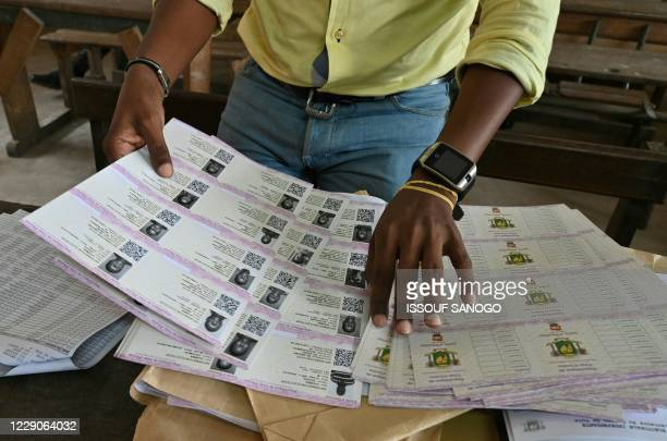 An Ivory Coast Electoral Commission official holds voting cards on October 14in Abidjan during distribution of voting cards ahead of the country's...