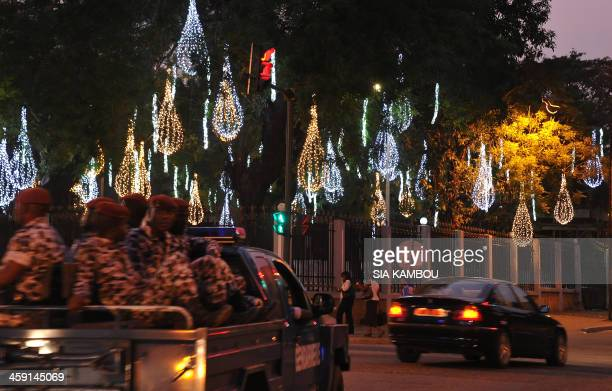 An Ivory Coast gendarmerie truck drives down a street decorated with Christmas lights in the Plateau business district of Abidjan on December 23 2013...