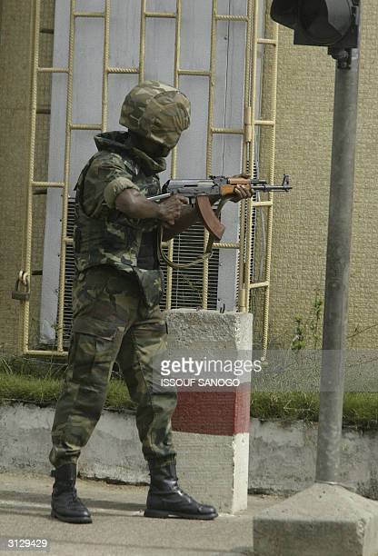 An Ivory Coast 's soldier holds his AK47 as he is on patrol in the Yopougon district Abidjan suburbs 25 March 2004 after demonstrators clashed with...