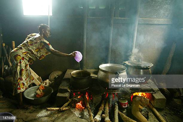 An Ivory Coast woman cooks at the Sainte Camille center for mentally ill after the local Red Cross distributed food October 14, 2002 in Bouake, Ivory...