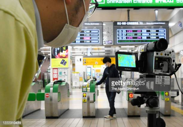 An Iwate Prefecture staff check the monitor of the thermography as passengers arrive at JR Morioka Station on May 1, 2020 in Morioka, Iwate, Japan....