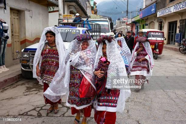An Ixil Maya bride center right and her family walk down a street in Nebaj Guatemala January 6 2019 The bride and her family wear wearing a...