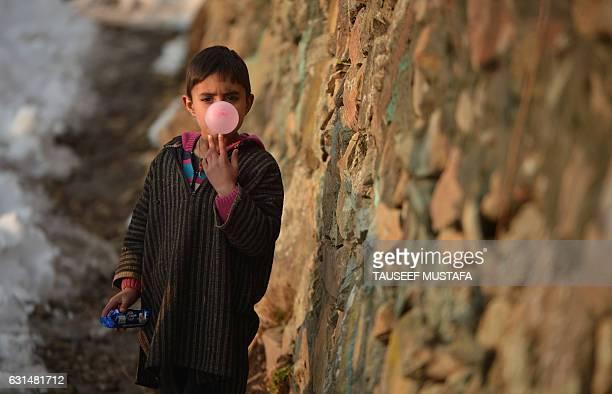 An Kashmiri boy blows a bubble as he chews gum in a neighbourhood on the outskirts of Srinagar following the season's first snowfall in Kashmir on...
