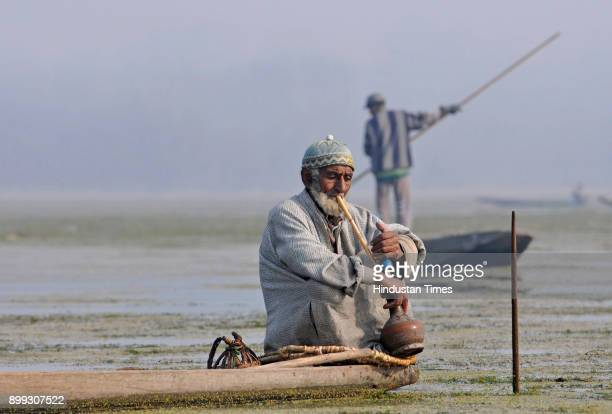 An Kashmiri fisherman smokes a hubble bubble or Hukka as he takes a break between catching fish with a harpoon in the waters of the Anchar Lake on...