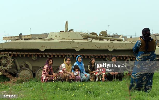 An Kurdish family have their photo taken in front of a tank used during the Saddam Hussein regime as hundreds commemorate the 25th anniversary of the...