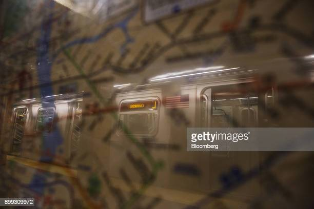 An L train subway car is reflected on glass covering a map at the 14th StreetUnion Square station in New York US on Thursday Dec 21 2017 New York's...