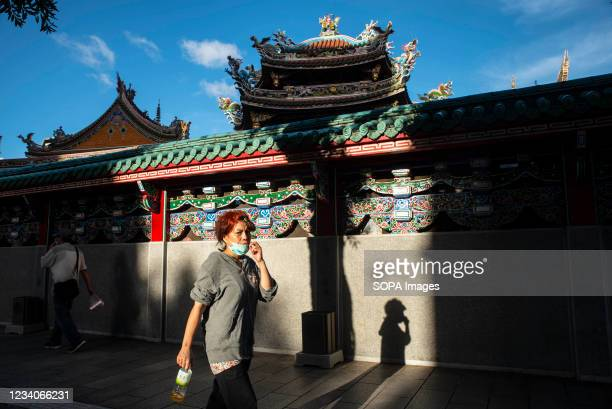 An lady wearing a face mask walks past a nearby temple in Wanhua. Local authorities of the two cities have made mask wearing in outdoor areas...