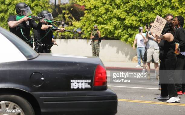 An LAPD officer aims a nonlethal weapon during a confrontation with protesters at a Black Lives Matter protest following the death of George Floyd on...
