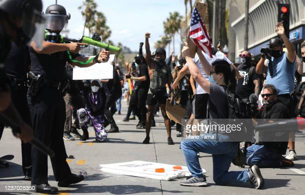 An LAPD officer aims a nonlethal weapon during a confrontation with protesters following the death of George Floyd on May 30, 2020 in Los Angeles,...