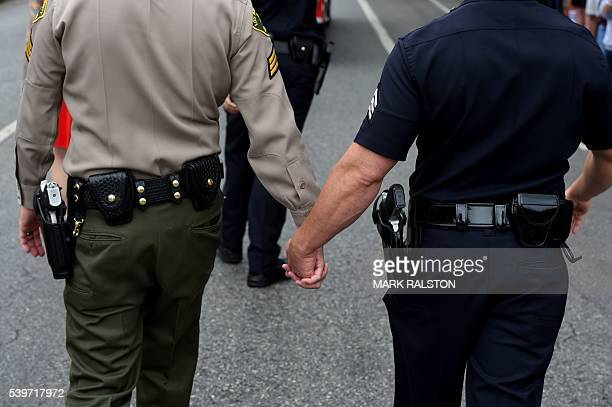An LAPD officer holds hands with a Sheriff's Deputy as they march during 2016 Gay Pride Parade in West Hollywood, California on June 12, 2016....