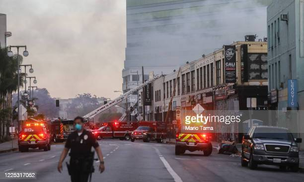 An LAPD officer keeps watch on a multiple structure fire as LAFD firefighters work following an explosion on May 16, 2020 in Los Angeles, California....