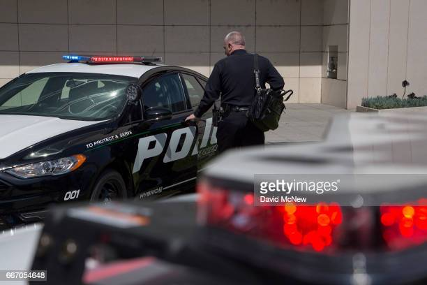 An LAPD officer looks at a car at the unveiling of two new Ford Fusion hybrid pursuitrated Police Responder cars at Los Angeles Police Department...